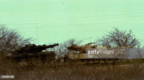 WACO TX MARCH 10 Two M1 Abrams tanks sit in the underbrush about 200 yards from the Branch Davidian cult compound in Texas 10 March 1993 Negotiations...
