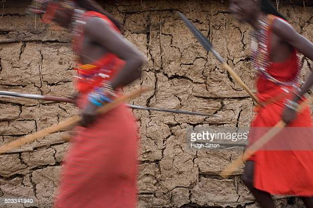 two maasai warriors running past mud hut - hugh sitton stock-fotos und bilder