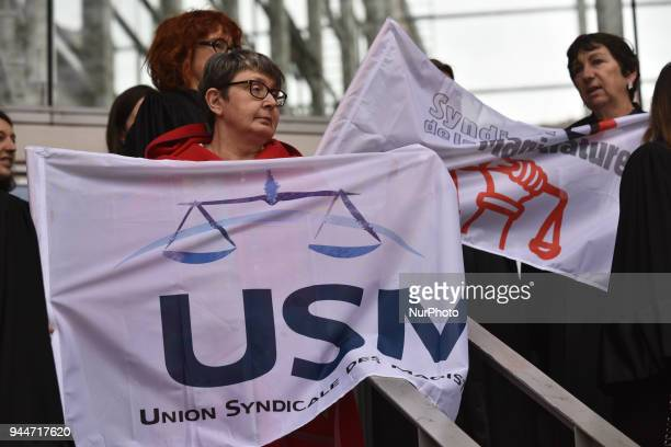 Two magistrates hold flags of their unio On the right USM ie Magistrates Trade Union On the left SM ie Magistrates Union The French Bar Association...