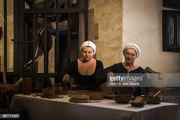 Two maids preparing food for a banquet in the kitchen of a castle 15th century Historical reenactment