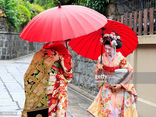 Two Maiko girls bowing on stone paved street