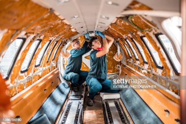 two maintenance mechanics repairing the interior of the jet airplane - repairing stock pictures, royalty-free photos & images