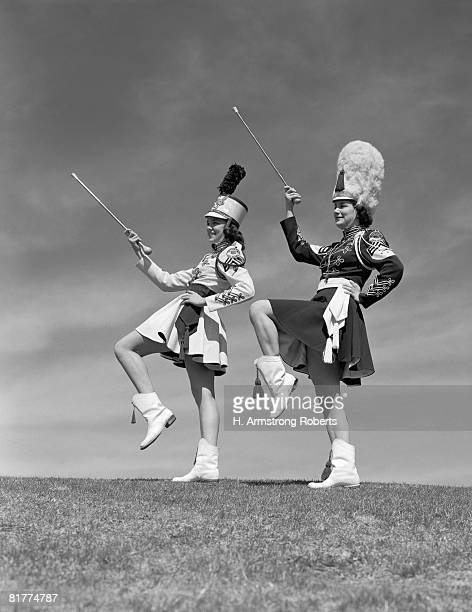 two majorettes in uniform doing routine with batons. - drum majorette stock pictures, royalty-free photos & images