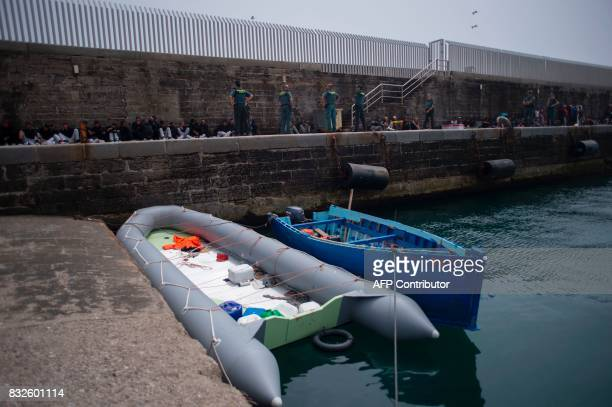 Two makeshift boats moor in foreground as wouldbe immigrants rest after being rescued in the waters of the Strait of Gibraltar in the port of Tarifa...