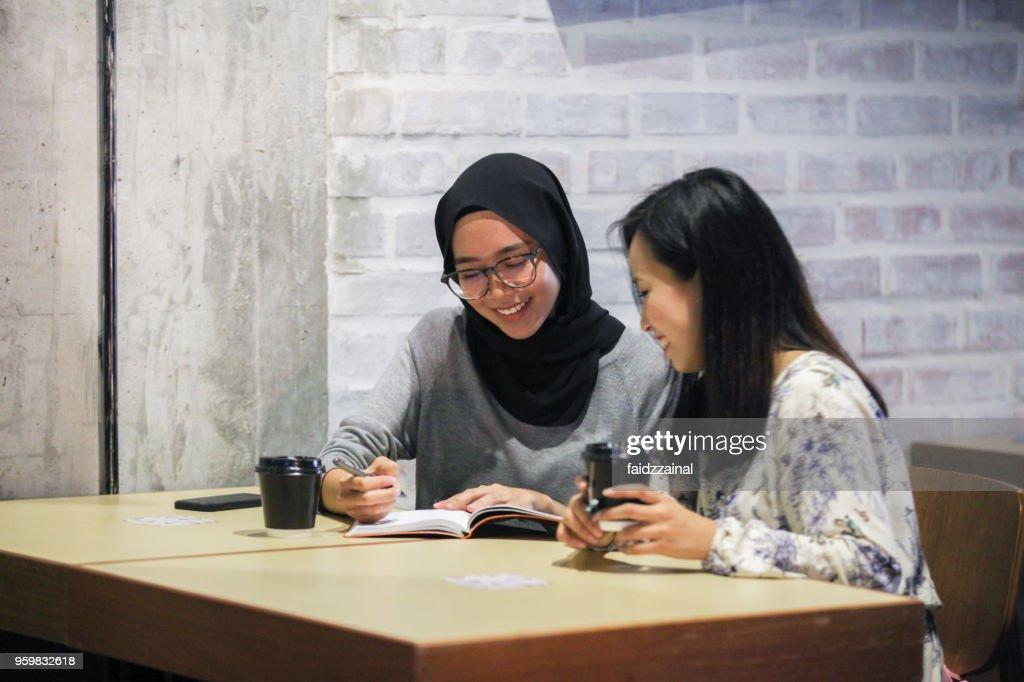 Zwei malaiischen muslimische Frauen diskutieren in einem Cafe : Stock-Foto
