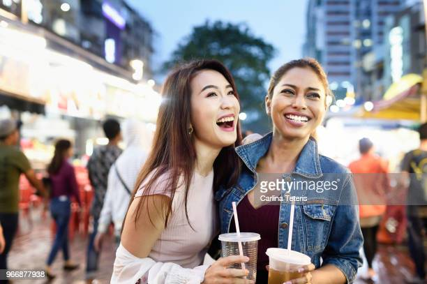 two malaysian woman with drinks at a night market - malaysian culture stock pictures, royalty-free photos & images