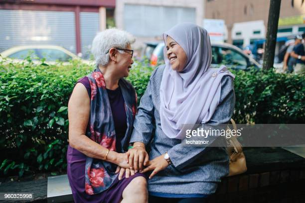 two malaysian women talking on the street of kuala lumpur - islam stock pictures, royalty-free photos & images