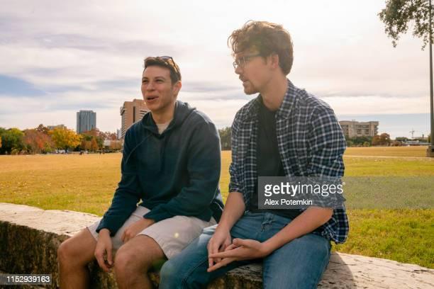 deux hommes environ 30-ans-vieux amis, latino et caucasien-blanc, s'asseyant et parlant dans le parc - 30 34 years photos et images de collection