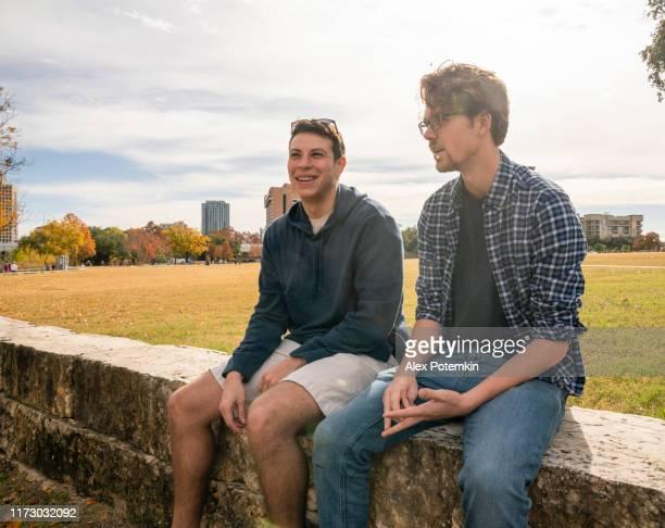 deux mâles environ des amis de 30 ans, latino et caucasien-blanc, s'asseyant et parlant dans le stationnement - 30 34 years photos et images de collection