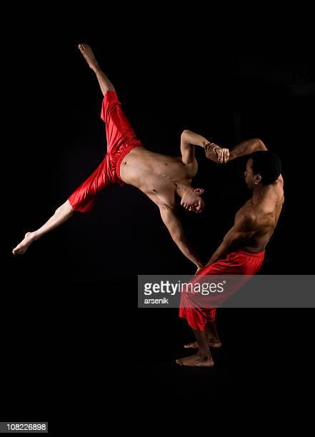 Zwei männliche Akrobaten posieren, isoliert auf Schwarz
