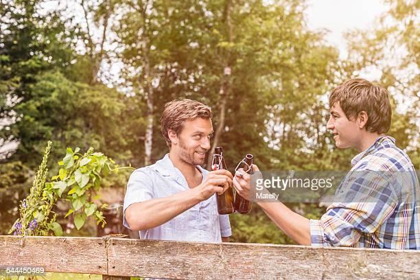 two male adult friends toasting with beer bottles at garden fence - nachbar stock-fotos und bilder
