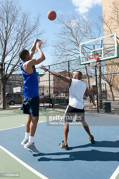 Two Male Adults Playing One on One Basketball