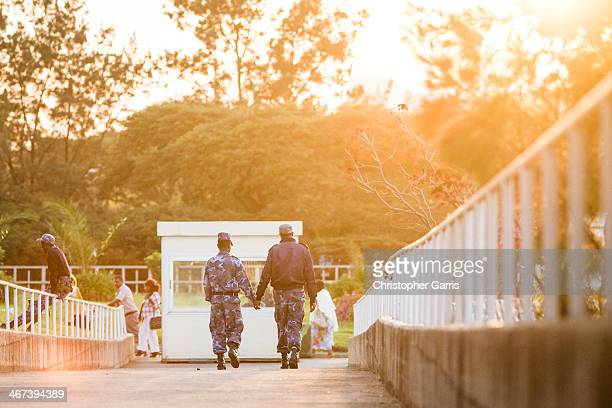 Two male airport security workers hold hands as they walk down a ramp in the evening light. Shot at the Addis Ababa international airport.