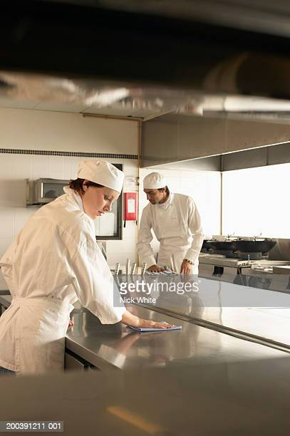 Two male and female cooks members cleaning kitchen surfaces