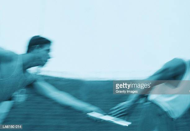 Two male athletes passing relay baton (blurred motion, toned B&W)