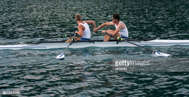 Two male athletes rowing across lake in late afternoon