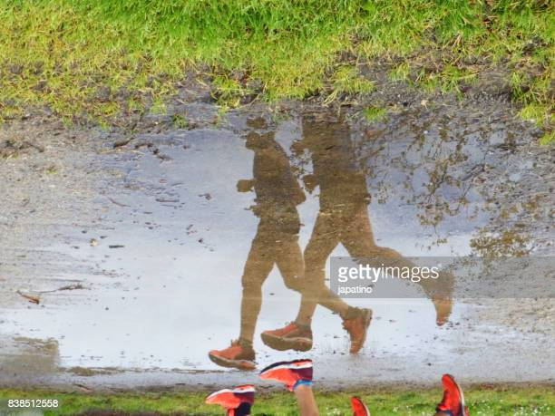 Two male athletes running reflected in a puddle of water