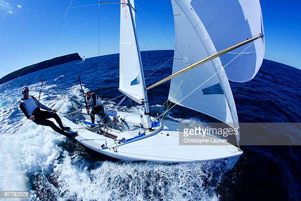 Two male athletes sail an Olympic class racing boat in Sydney Harbor, Australia.