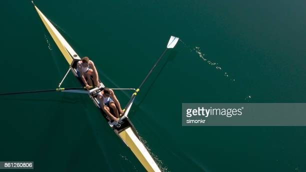 Two male athletes sculling on lake in sunshine