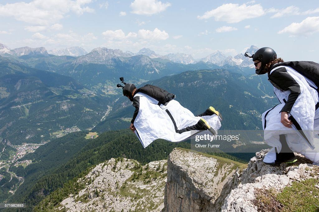 Two male BASE jumpers exiting from mountain top, Dolomites, Italy : Stock Photo