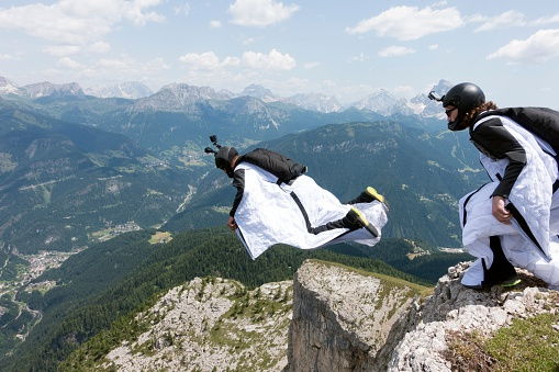 Two male BASE jumpers exiting from mountain top, Dolomites, Italy - gettyimageskorea