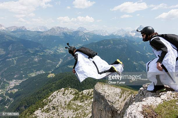 two male base jumpers exiting from mountain top, dolomites, italy - position stock-fotos und bilder