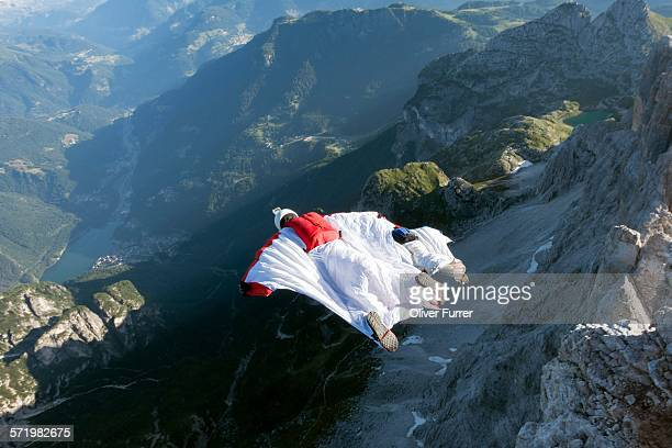 Two male BASE jumpers wingsuit flying from mountain, Dolomites, Italy