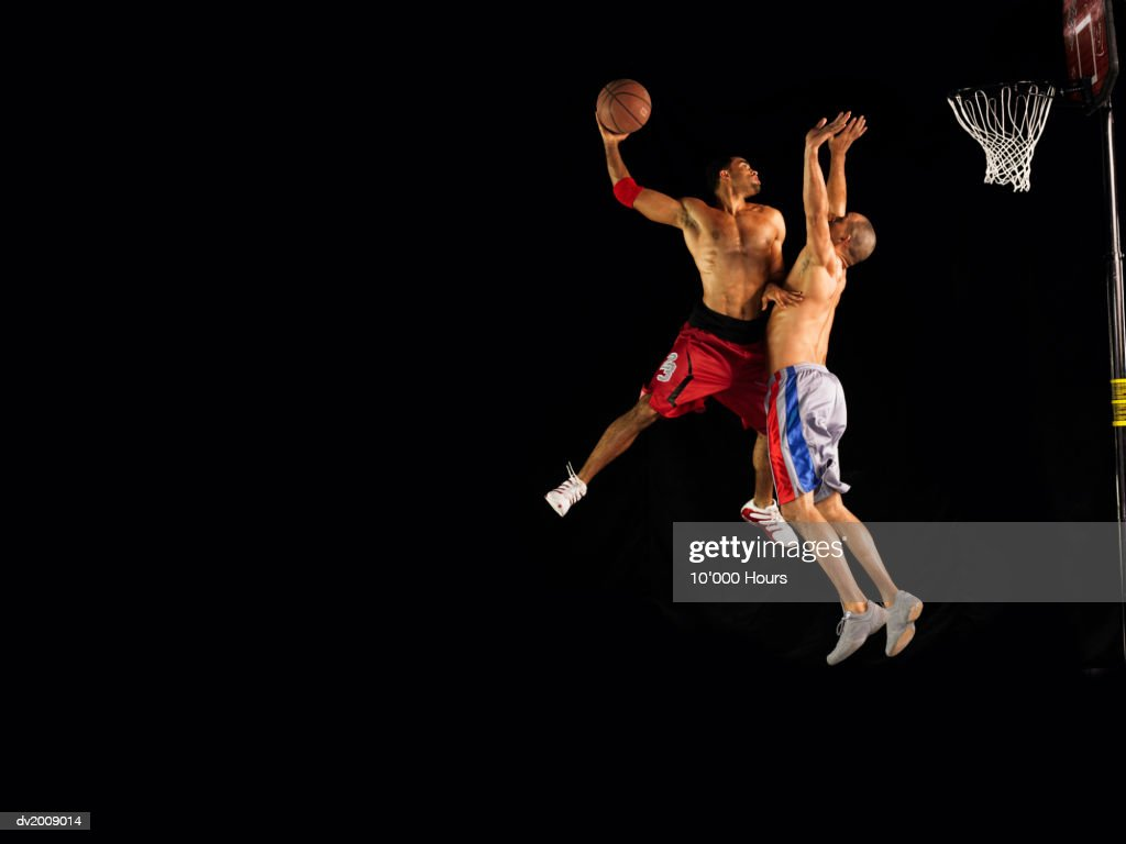 Two Male Basketball Players Jumping Mid Air, One Aiming for the Hoop, the Other One Defending : Stock Photo