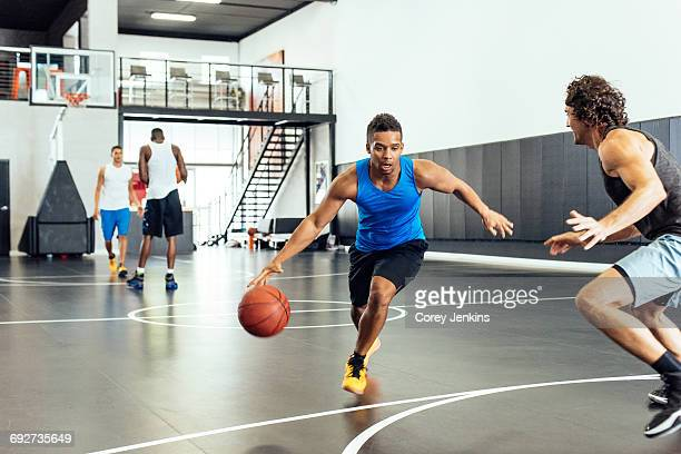 Two male basketball players practicing ball defence on basketball court