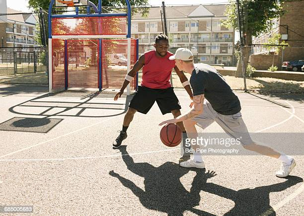 Two male basketball players practising on basketball court