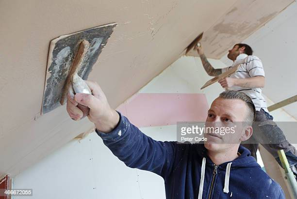 Two male builders plastering house