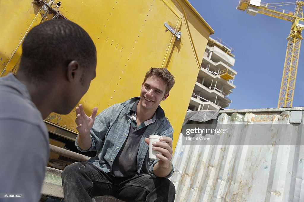Two Male Builders Sit in a Building Site Having a Tea Break and a Chat : Stock Photo