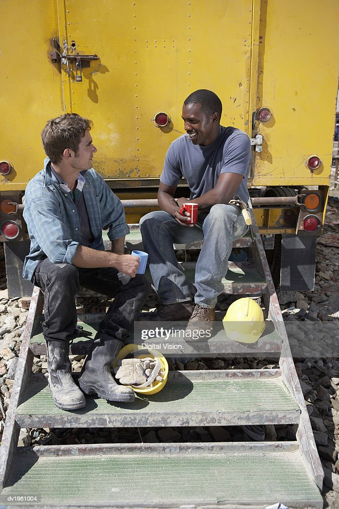 Two Male Builders Sit on the Steps of a Construction Vehicle, Having a Tea Break and Chatting : Stock Photo