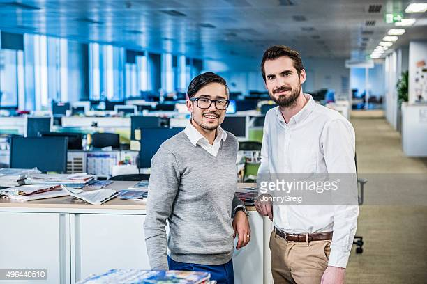 Two male business colleagues in modern office, portrait