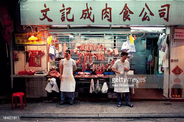 Two male butchers selling fresh meat stand waiting for customers outside their street market stall in Hong Kong.
