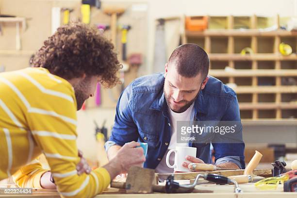two male carpenters in a construction workshop, working together - izusek stock pictures, royalty-free photos & images