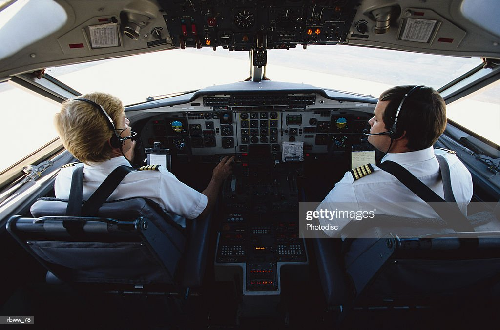 two male caucasian pilots are sitting in the cockpit of an airplane : Foto de stock