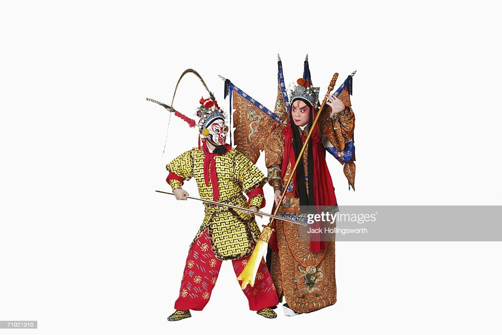 Two male Chinese opera performers gesturing with weapons : Stock Photo
