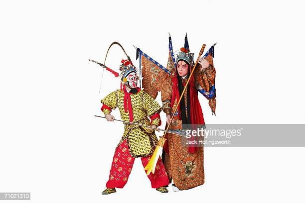 Two male Chinese opera performers gesturing with weapons