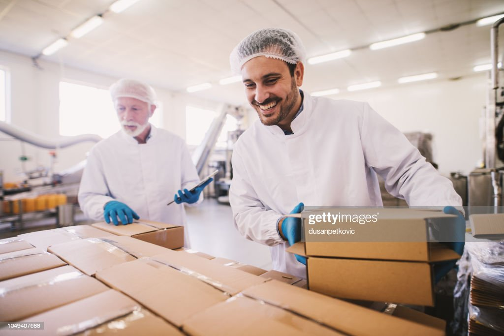 Two male colleagues i sterile clothes preparing boxes with products for transport. Standing in bright room or warehouse and counting package. : Foto de stock