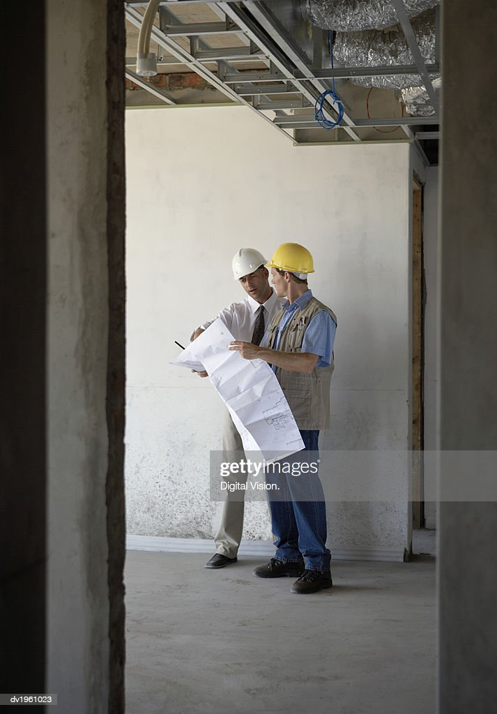 Two Male Construction Workers Stand in a Building Site Discussing a Blueprint : Stock Photo