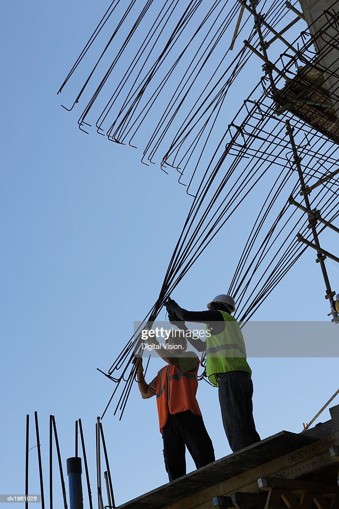 Two Male Construction Workers Stand on a Roof, Bending a Frame Into Position : Foto de stock