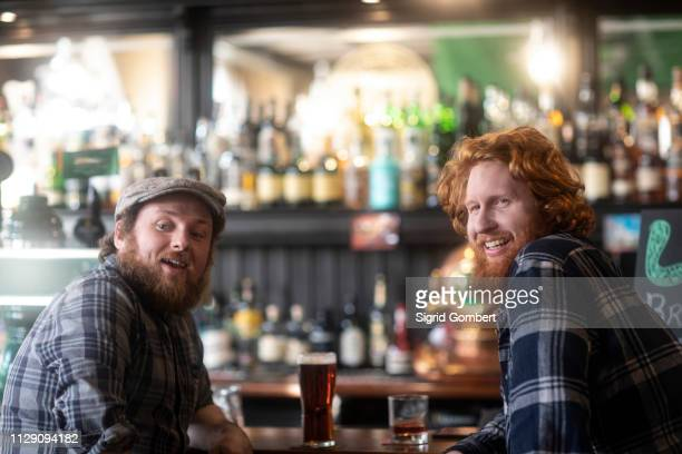 two male customers looking over their shoulders from bar in traditional irish public house - cultura irlandesa - fotografias e filmes do acervo