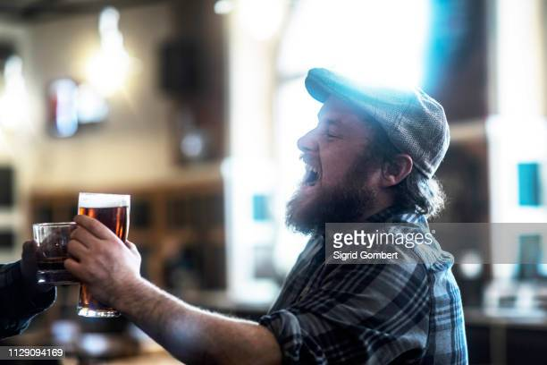 two male customers making a toast in traditional irish public house - sigrid gombert stock-fotos und bilder