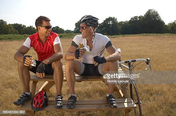 Two male cyclists sitting on picnic table, eating