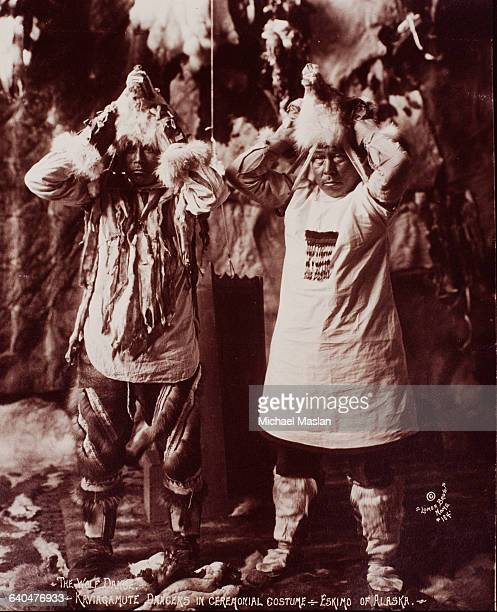 Two male dancers put on wolf heads prior to performing a ceremonial dance