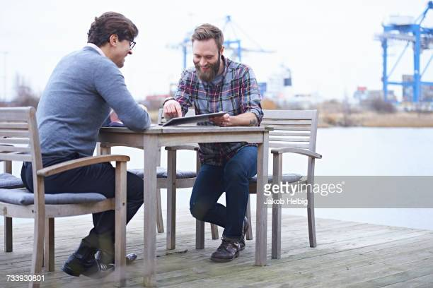 Two male designers having meeting on waterfront outside design studio