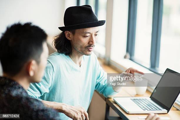 Two male designers working in cafe