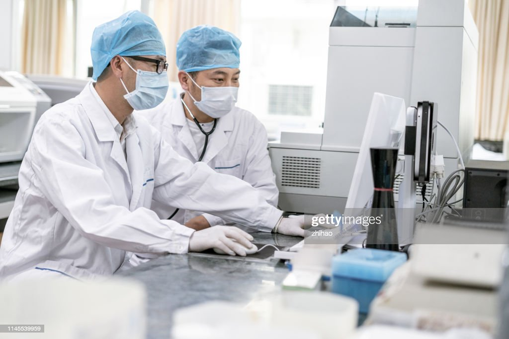Two male doctors discussing work in front of a computer in a hospital laboratory : Stock Photo