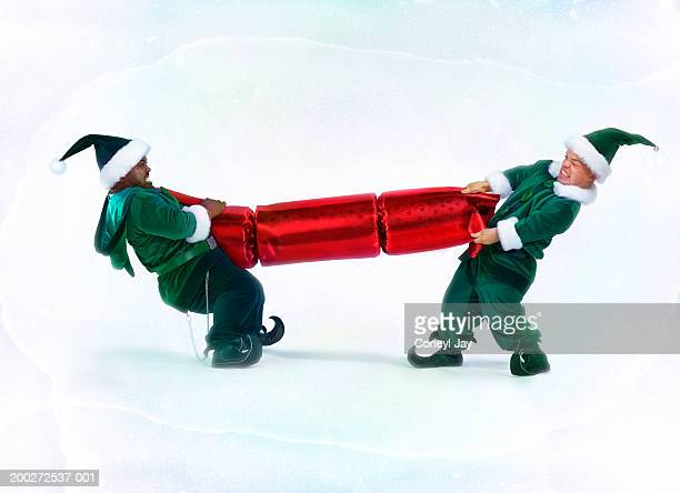 two male 'elves' pulling large christmas cracker (digital enhancement) - black dwarf stock pictures, royalty-free photos & images